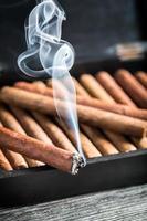 brennende Zigarre auf hölzernem Humidor voll mit Zigarren foto
