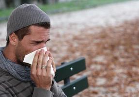 Mann putzt sich die Nase foto