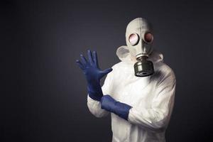 Mann mit einer Gasmaske, die seine Handschuhe anzieht foto