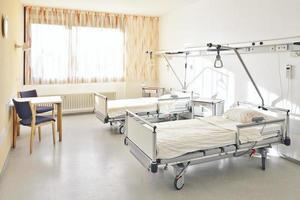 Krankenzimmer mit zwei Betten und einem Tisch mit zwei Stühlen foto