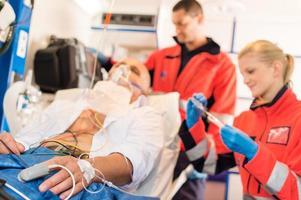 kranker Patient, der von Sanitätern in einem Krankenwagen behandelt wird foto