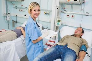 Krankenschwester schaut in die Kamera neben transfundierten Patienten foto