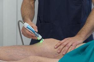 Physiotherapeut, der das Knie eines Patienten bei der Rehabilitation unterstützt foto