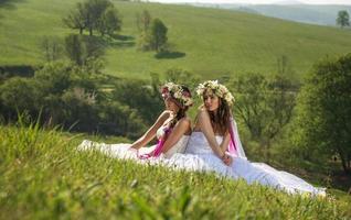 2 schöne Braut im Freien, auf Gras sitzend foto