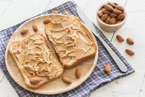 Erdnussbutter auf Holzteller mit Nüssen auf Holztisch foto