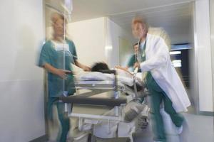 Ärzte bewegen Patienten auf Trage durch Krankenhauskorridor foto