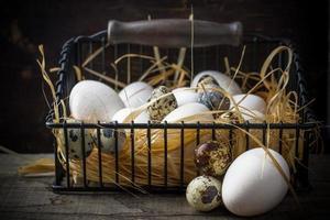 Korb mit frisch gelegten Eiern auf Stroh liegend in der foto