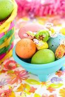 farbige Ostereier und Süßigkeiten in der blauen Schüssel