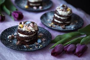 Schokoladen-Osterkuchen-Honig-Mascarpone mit lila Tulpen foto