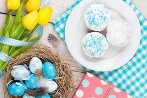 Ostern mit Eiern, gelben Tulpen und traditionellen Kuchen foto