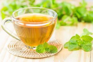 Tee mit Minze auf Holzachterbahn, warme Tönung, selektiver Fokus foto