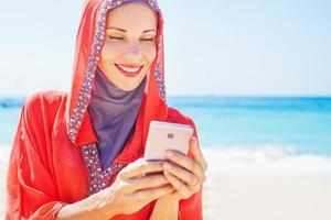 Frauen im roten Kapuzenkleid mit Telefon am Strand foto