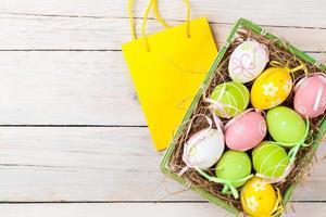 Osterhintergrund mit bunten Eiern und Geschenktüte foto