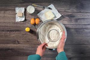 Backtisch mit Mehl, Eiern und einer Frau, die Teig vorbereitet. foto