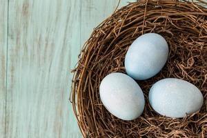 drei blaue Ostereier in einem Nest foto
