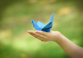 Papierkranich an der Hand des kleinen Mädchens