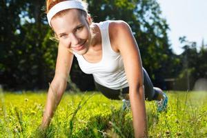 junge Frau, die Liegestütze auf grünem Gras tut. foto