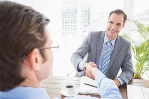 lächelnder Geschäftsmann, der einem Mitarbeiter die Hand schüttelt foto