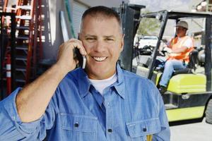 Arbeiter, der auf Handy mit Mitarbeiter im Hintergrund kommuniziert foto