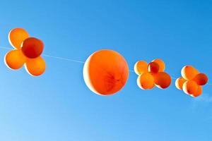 orange Luftballons gegen einen blauen Himmel foto
