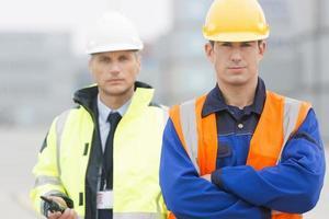 Porträt des selbstbewussten Arbeiters, der mit Mitarbeiter im Versandhof steht foto