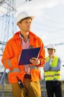 männlicher Architekt mit Zwischenablage, die vor Ort arbeitet, während Mitarbeiter steht