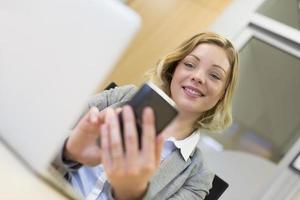 hübsche Geschäftsfrau auf Handy im Büro, SMS, Nachricht foto