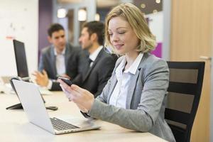 süße Geschäftsfrau auf Handy im Büro, SMS, Nachricht foto