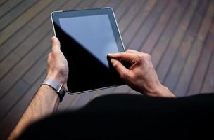 Hände des jungen Hipster-Mannes, die mit Touchscreen-Gerät stöbern foto