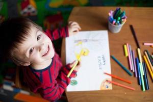 entzückender kleiner Junge, Bild für Ostern zeichnend foto