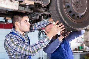 konzentrierte erwachsene Mechaniker, die Auto reparieren foto