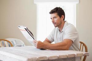 konzentrierter junger Mann, der Zeitung liest foto