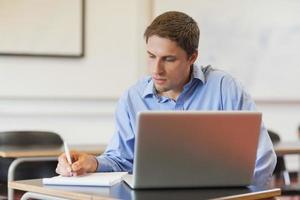 konzentrierter männlicher reifer Schüler, der sein Notizbuch zum Lernen benutzt