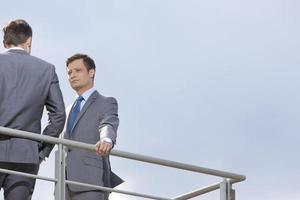 junger Geschäftsmann, der Mitarbeiter gegen klaren Himmel betrachtet foto