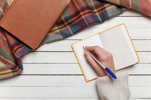 weibliche Hand, die etwas in Notizbuch schreibt foto