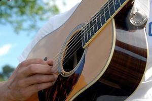 Person, die draußen Gitarre spielt foto