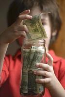 Kind, das seine Ersparnisse in Dollar für die Zukunft behält foto