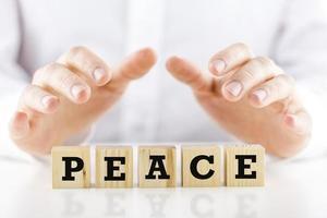 Mann, der schützende Hände über dem Wort Frieden hält foto