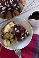 Kuchenstücke mit Schokoladensauce, Preiselbeeren und Mandelblättchen foto