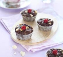 Schokoladenmuffins mit weißen Schokoladenstückchen und Himbeeren foto