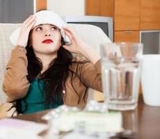 leidende Frau betäubt Handtuch zum Kopf