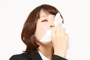 junge Geschäftsfrau mit einer Allergie, die in Gewebe niest foto