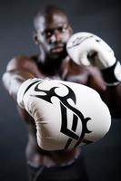 junger athletischer Boxer, der Handschuhe im schwarzen Hintergrund trägt.