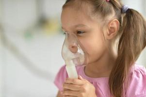 schönes kleines Mädchen mit Inhalator foto
