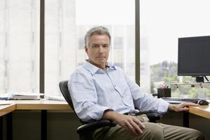 Geschäftsmann sitzt im Büro foto