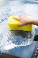 Handwäsche Windschutzscheibe mit gelbem Schwamm foto