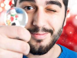 glücklicher junger Mann, der Weihnachtsball hält.
