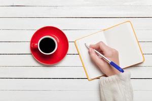 weibliche Hand, die etwas in Notizbuch nahe Tasse Kaffee schreibt.