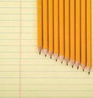 Reihe gelber Stifte auf Notizblock foto