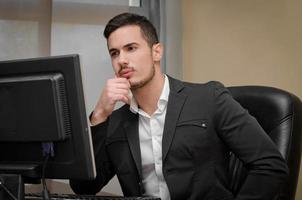beschäftigter, besorgter junger männlicher Büroangestellter foto